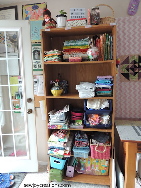 organized quilt room bookcase fabric display