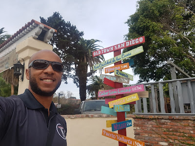 Tim in front of a sign with directional arrows pointing to many different locations