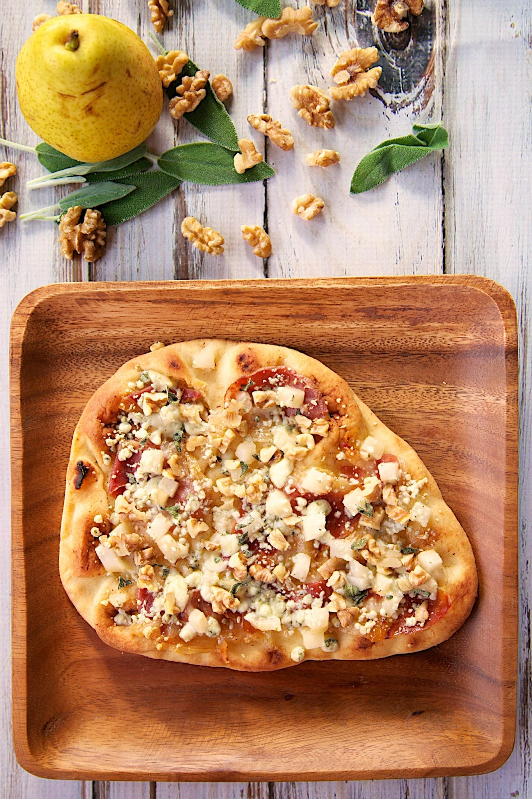 Pear & Gorgonzola Flatbread Recipe - Naan flatbreads topped with browned butter, pears, prosciutto, gorgonzola, walnuts and sage - the flavor combination is delicious! We ate these twice in one week!