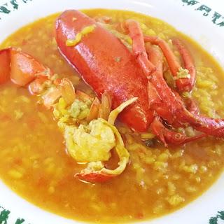 un plato de arroz meloso con medio bogavante