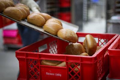 frische Brötchen der Bäckerei Ihr guter Liebig werden von Hand in einen Korb abgeschüttet