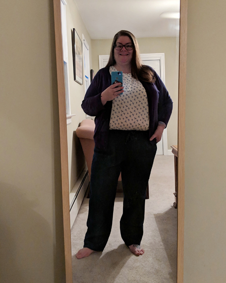 image of me standing in a full-length mirror, smiling, with my hair down, wearing grey-framed glasses, a navy cardigan, a pink patterned blouse, and blue drawstring trousers