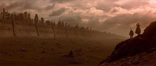 Dusty desert scene showing walls of Mega-City One with travellers observing
