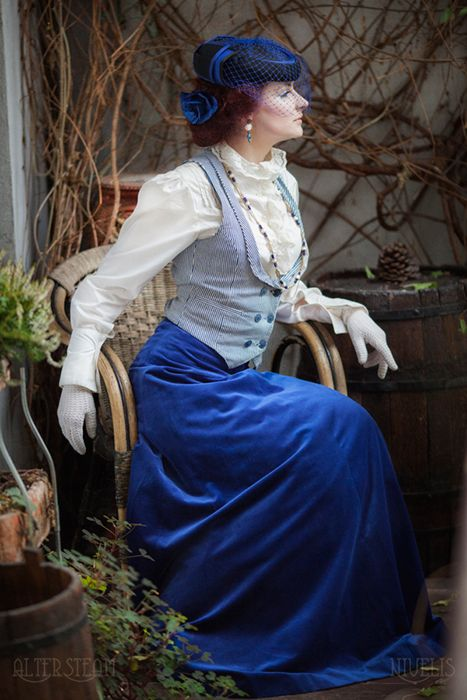 Woman in Victorian clothing (day dress). White high neck frilly victorian blouse, black and white vest, long sapphire blue skirt, white gloves, blue hat with blue bird cage veil, earrings and necklace. Neo-Victorian fashion for women