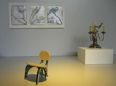 Modern miniature gallery space with a one-of-a-kind chair displayed in front of  a candelabra on a plinth, and a triptych on the wall.