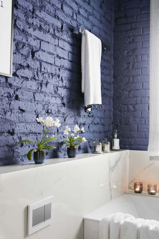 Baño con pared de ladrillo visto pintada