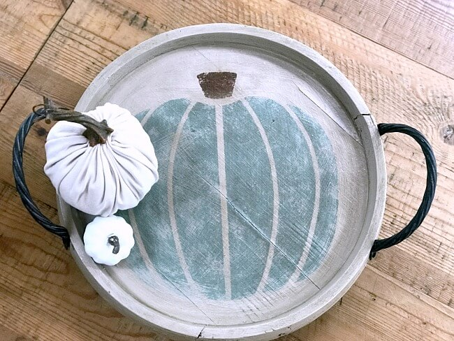 Round stenciled pumpkin tray with 2 white pumpkins on it
