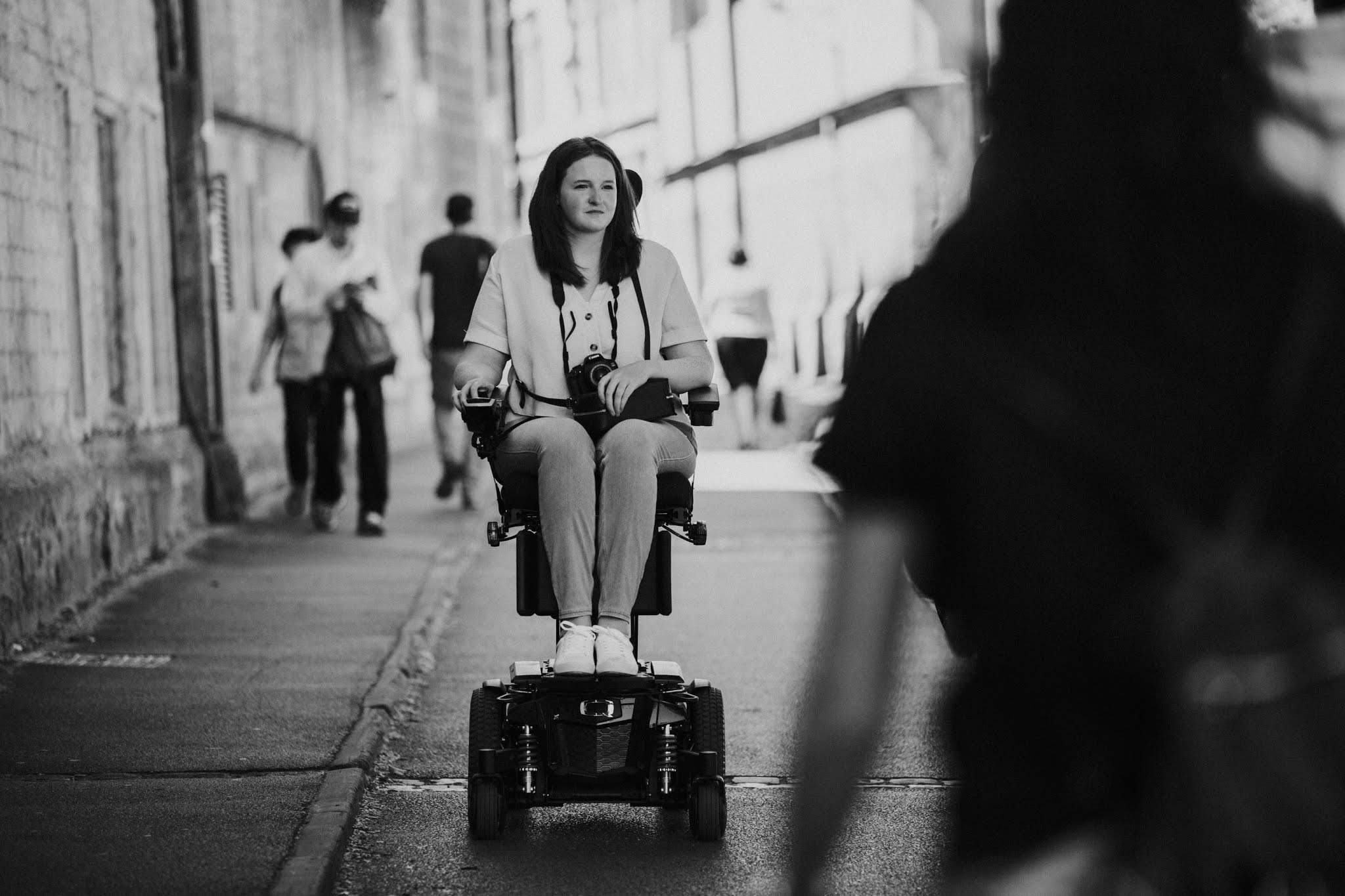 The photo is black and white. Shona, a young woman using a powerchair which is raised up to eye level height, is wheeling down an old cobbled road. Other people are out of focus walking near her.
