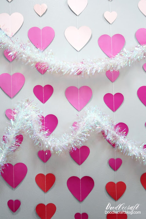 Ombre hearts in light pink, hot pink and red with holographic tinsel garland make the perfect Valentine backdrop or photo op.