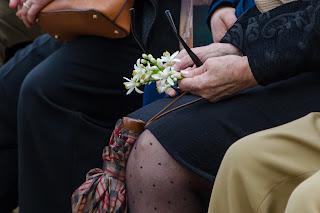 Foto de las manos de una señora, solo se le ve eso, y en las manos tiene un paraguas cerrado, azahar y gafas de sol. Imagen típica de Sevilla donde no sabes qué vas a necesitar en cada momentos.