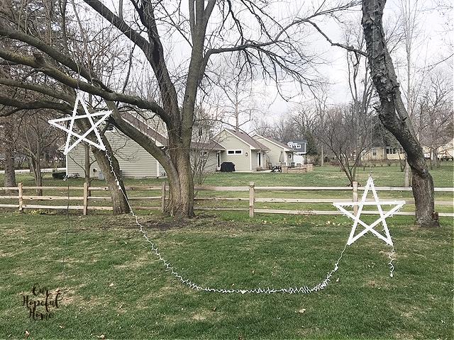 back yard split rail fence hanging white wooden Christmas stars