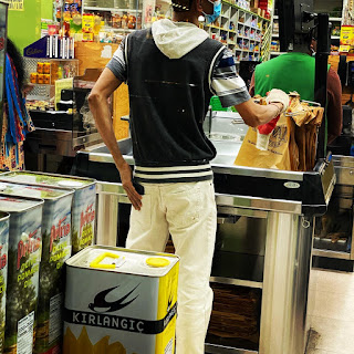 A bagger at a grocery store on 74th Street in the Jackson Heights neighborhood of Queens checks his back-pocket.