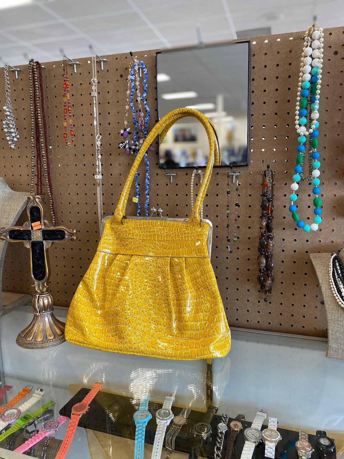 Yellow Thrifted Handbag Sitting On The Shelf At Goodwill
