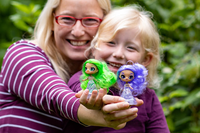 Mother and daughter smiling and holding a Crystalina doll each