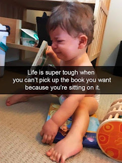 "Meme of child crying while sitting on a book that says ""Life is super tough when you can't pick up the book you want because you're sitting on it."""