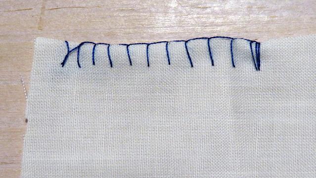 Punto festón con hilo azul sobre tela blanca por el derecho