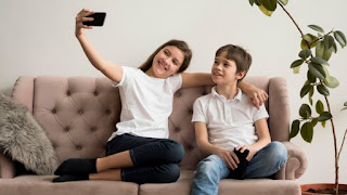 Siblings taking selfies