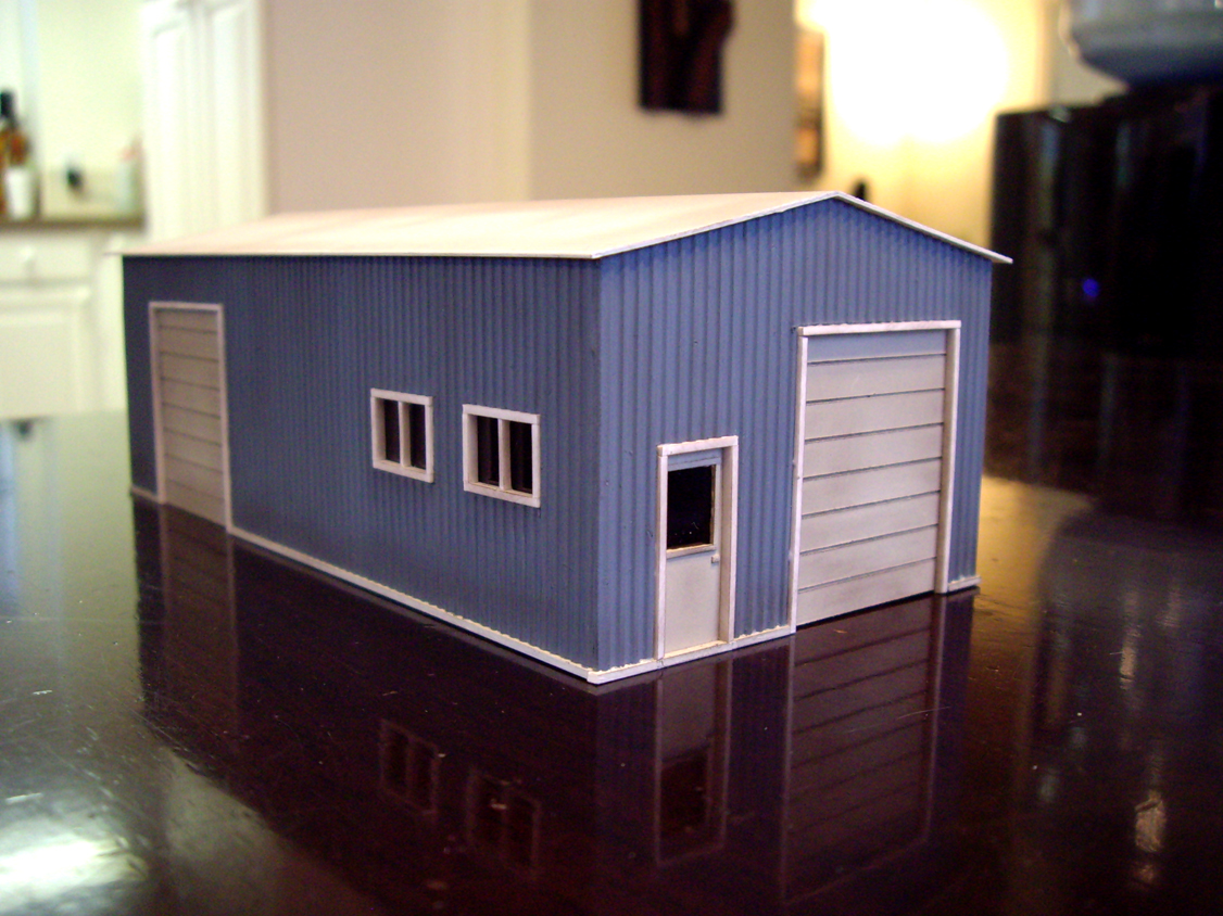 Scratch built styrene garage structure with blue walls and white doors, windows, and roof