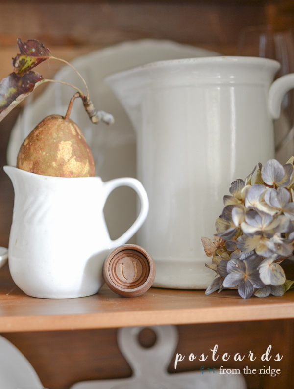 white creamer with pear on top, vintage wooden butter mold in antique oak hutch