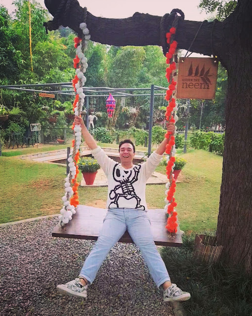Amit Anand, Editor Diverse Customer enjoying a moment on a swing decorated with flowers and smiling ear to ear. Amit is wearing a white Tokidoki sweater and sky blue Topman jeans, celebrating the onset of January 2021.