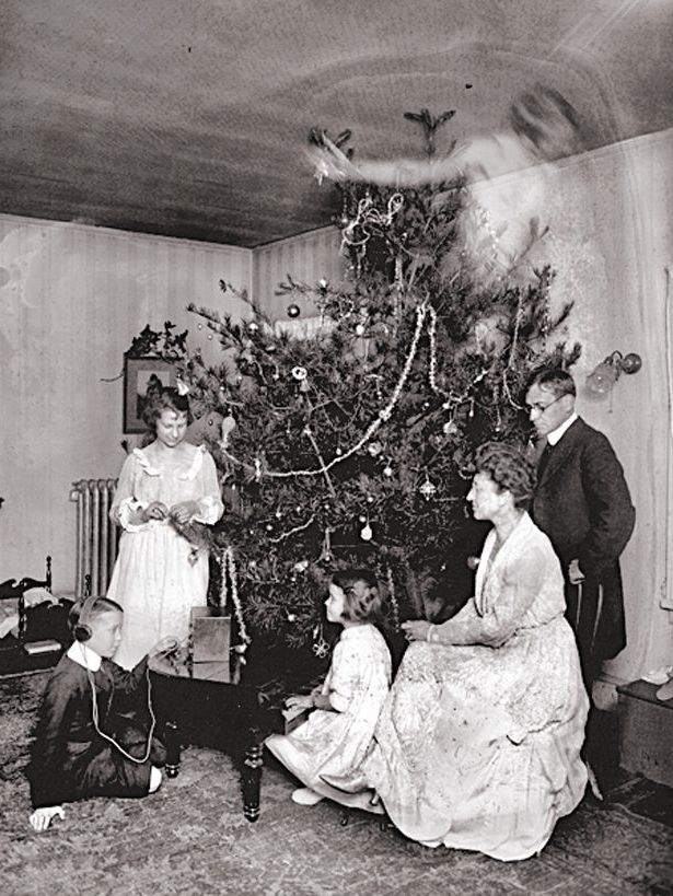 Victorian trick photography. Ghost girl appears while family surrounds the Christmas tree. The Cristmas Story Explained and other stories of Christmas Creepers. marchmatron.com