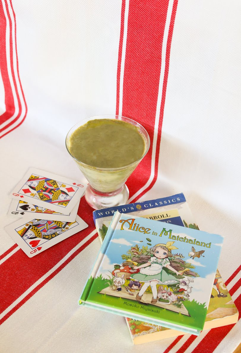 Pudding in a conical glass container and a red and white striped background, with both Alice in Matchaland and Lewis Carroll's books in background