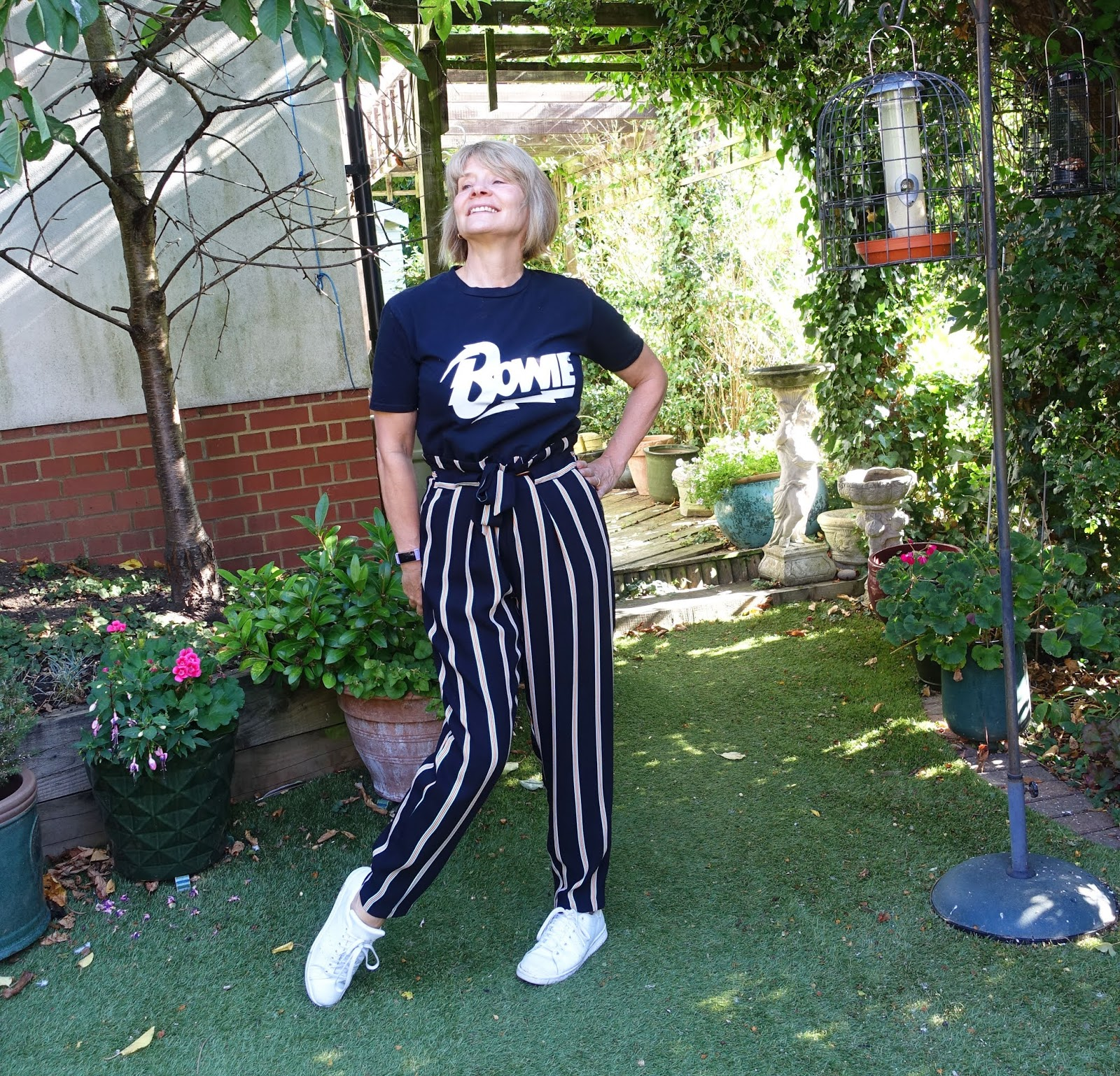 Over 50 style blogger Gail Hanlon from Is This Mutton wearing striped paper bag trousers - black Bowie tee and white Stan Smith trainers