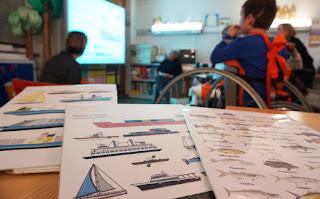Primeiro plano das placas com os vários tipos de barcos e peixes