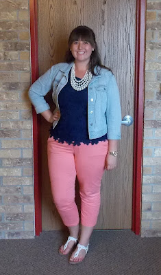 an outfit with a navy tank, coral chinos, a denim jacket, and a multistrand pearl necklace