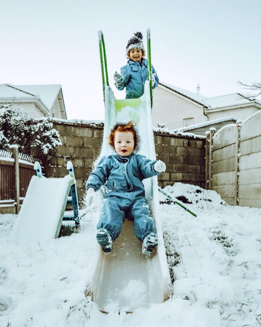 Two children on a slide in the snow