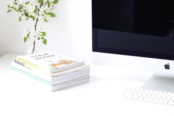 Mesa branca com computador e livros empilhados