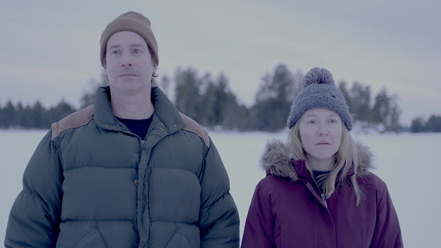 rob huebel and rachel harris stand in the snow