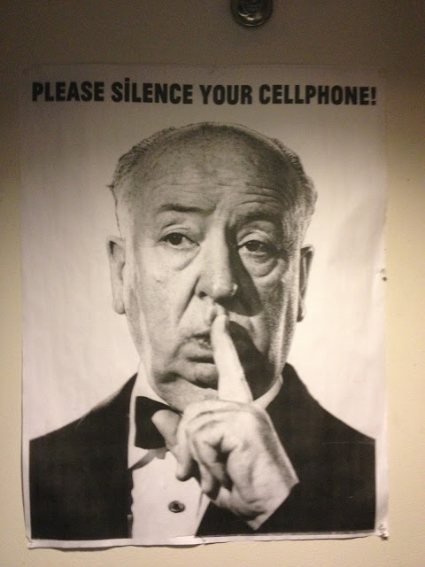 "A ""please silence your cellphones"" poster featuring Alfred Hitchcock from the Brattle Theatre in Harvard Square."