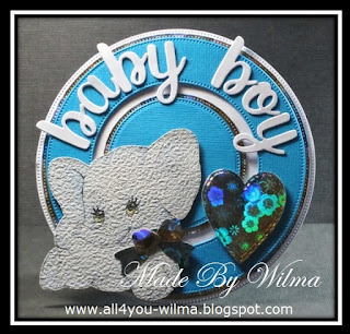 Een blauw-wit babykaartje met een olifantje van behangpapier met een glimmende strik en een glimmend hart. A blue and white baby card with an elephant made of wallpaper with a shiny bow and a shiny heart.