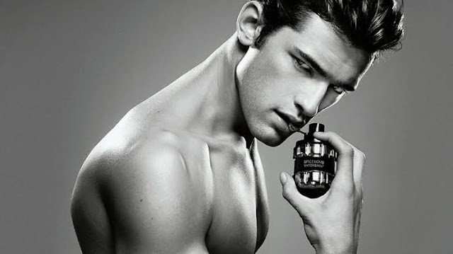 A man using cologne on his body