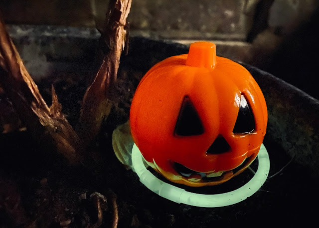 A plastic hollow pumpkin which opens to hide treats in, sitting in a flower pot and lit up by a glowstick