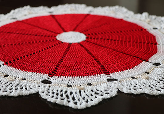 Crocheted cotton doily of 12 Santa faces with red hats on a dark background.