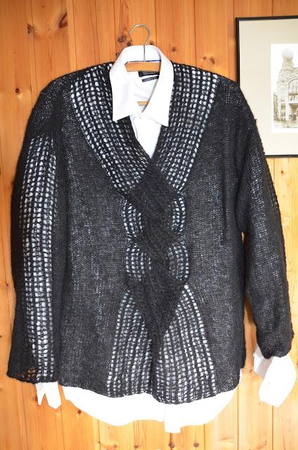 Czarny dziergany sweter z ażurowym warkoczem na środku i rękawach