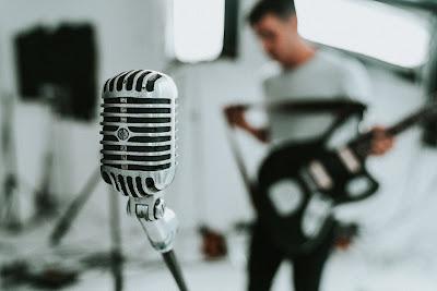 Micrófono y músico con su guitarra en segundo plano