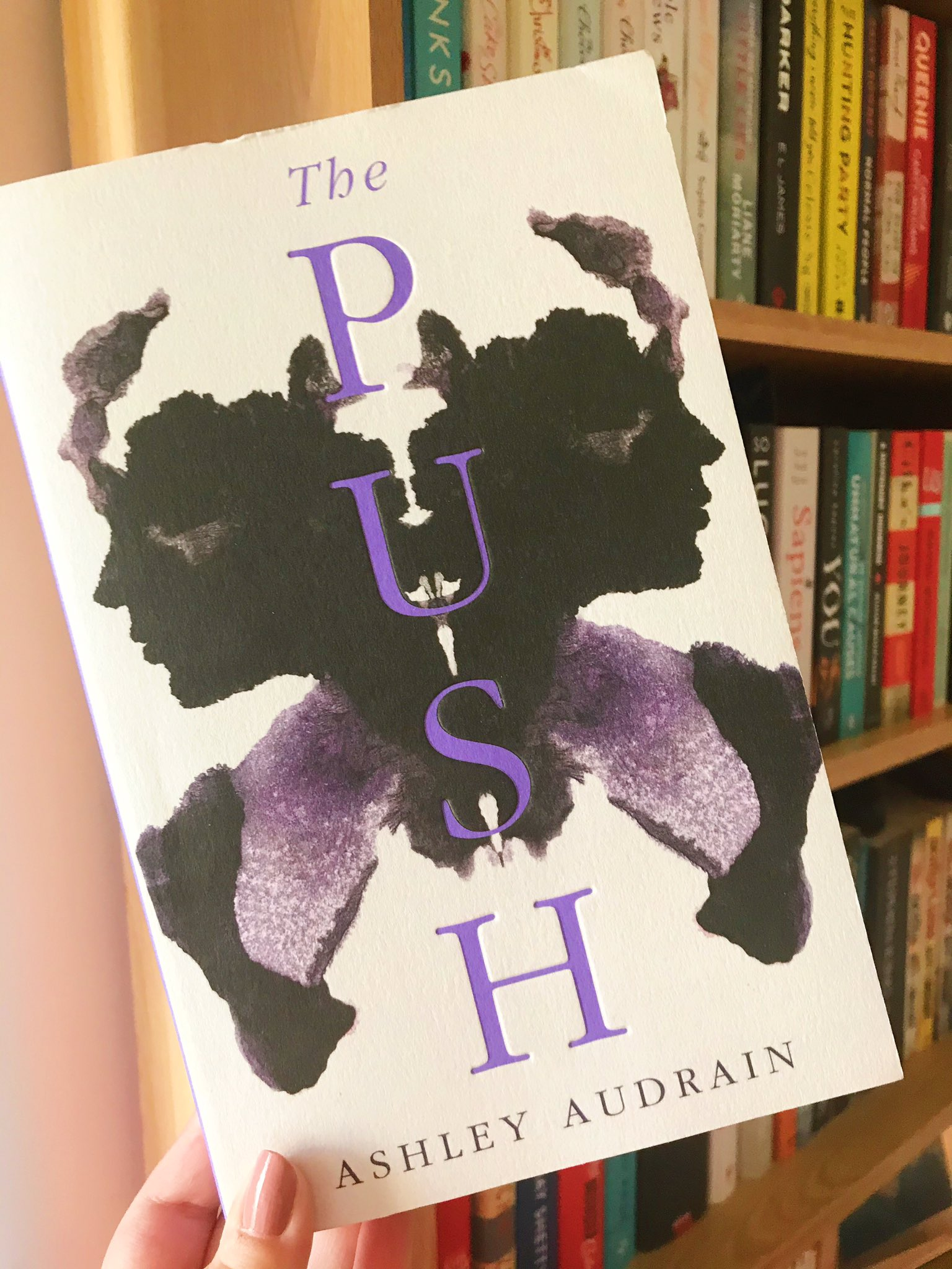 The Push by Ashley Audrain book held up in front of bookshelf