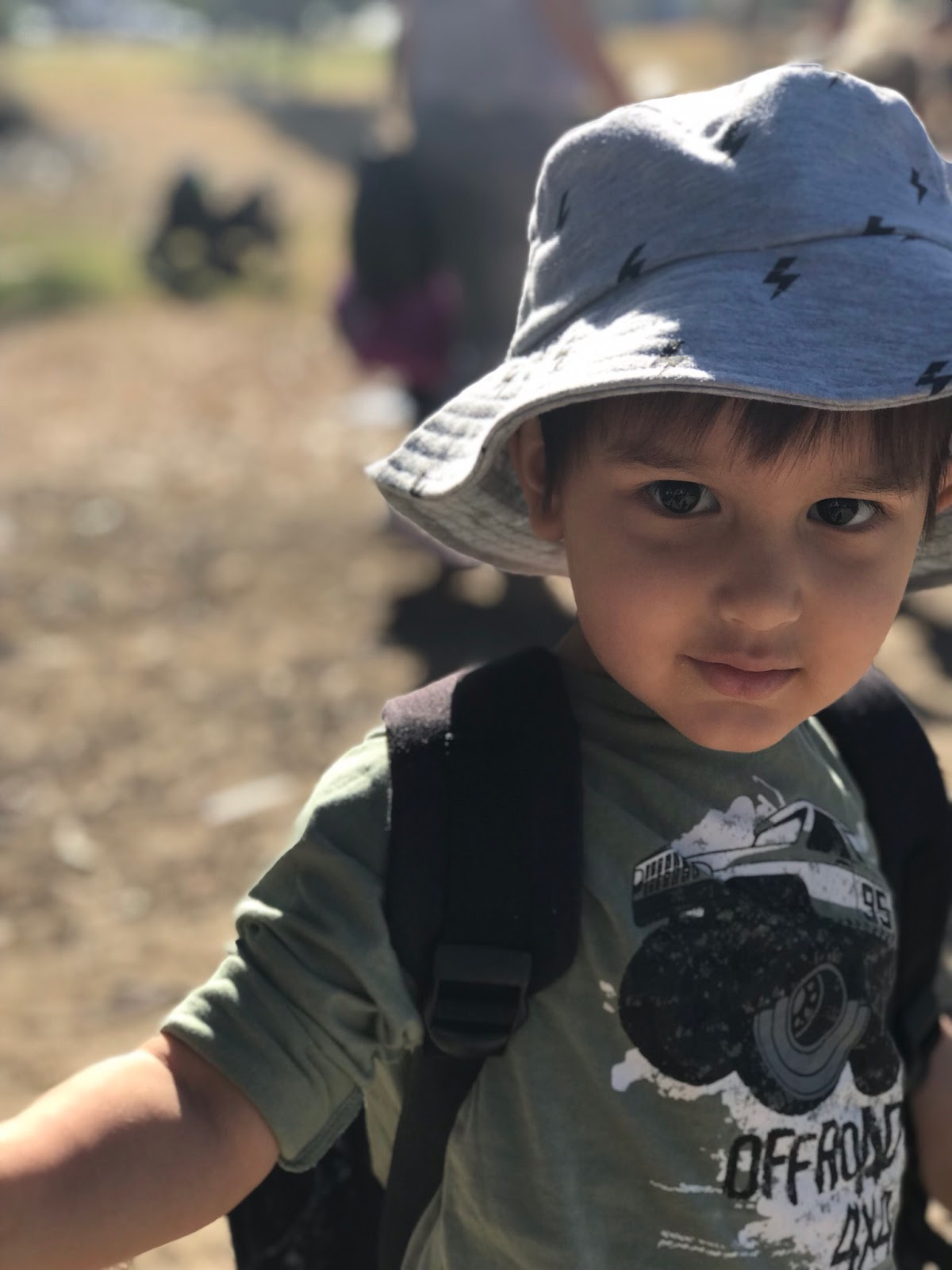 Image is a close-up photograph of a mixed race Asian toddler who is looking directly at the camera. He is wearing a grey wide brim hat, and an olive green long sleeve top. He is also wearing a backpack, although only the black shoulder straps are visible.