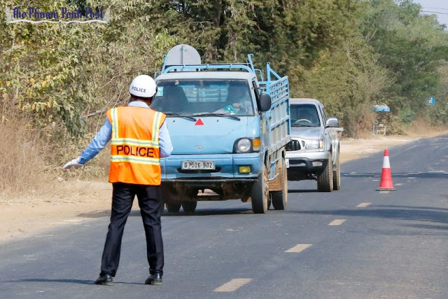 A police officer pulls over a truck earlier this year during a traffic stop on National Road 6 after the new law came into force. Heng Chivoan