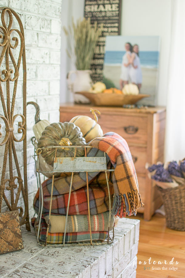 plaid scarves in a vintage wire egg basket, on a fireplace mantel