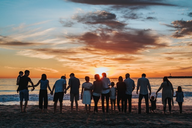 A group of people on a beach at sunset supporting each other