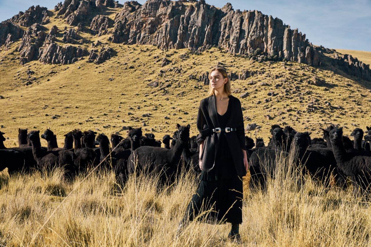 Mujer en medio de campo de alpacas negras con colección Black Alpaca de Kuna