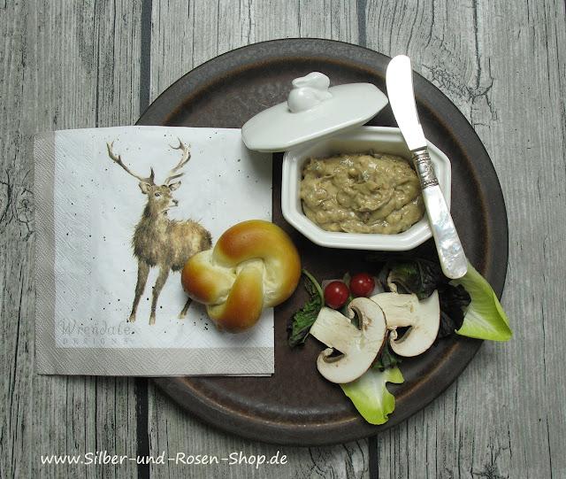 Pilzbutter, als Vorspeise für ein Jagdmenü, hübsch angerichtet in einer Portionsterrine. Dazu gibts ein Laugengebäck. Den Teller mit Cranberries, Champignonscheiben und Salat dekorieren und eine schöne Serviette mit Hirsch dazu legen.
