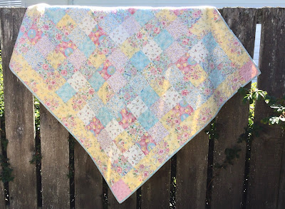 A simple quilt made from five inch charm squares