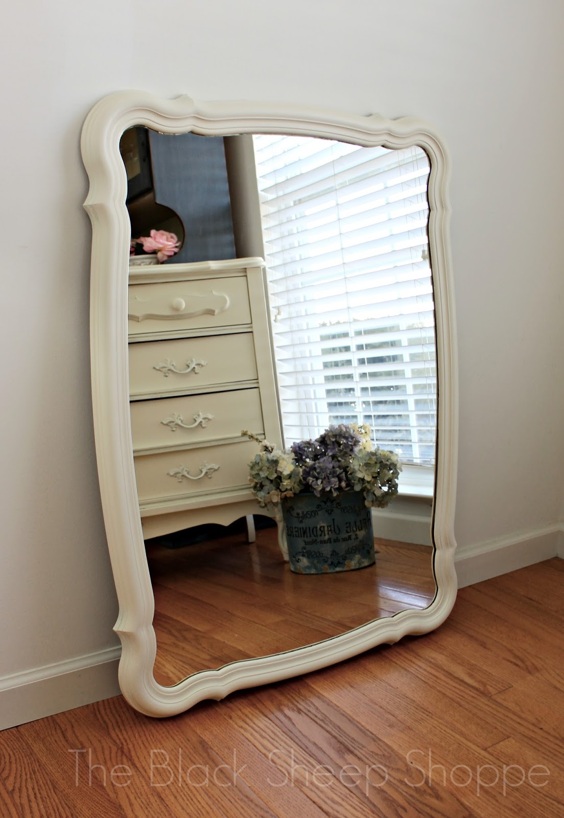 Mirror with dresser and flowers reflected in the background
