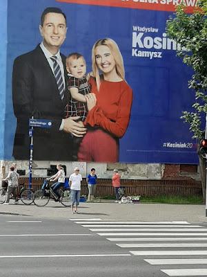 Wielkowymiarowy billboard pokazujący rodzinę Kosiniaków wisi na ścianie budynku w mieście