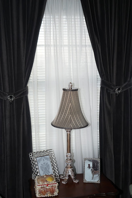 Grey velvet curtains, picture frame, seashell jewelry box, photo of dog
